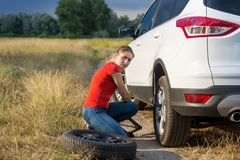 Young upset woman lifting her broken car with jack to change flat tyre on countryside road. Upset woman lifting her broken car with jack to change flat tyre on Royalty Free Stock Image