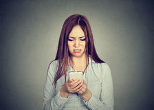 Upset woman looking at cellphone displeased with message she received royalty free stock image