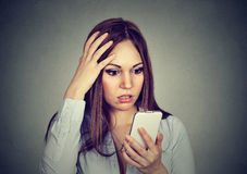 Upset woman looking at cellphone worried with message she received Royalty Free Stock Image