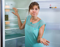 Upset woman looking at empty refrigerator Royalty Free Stock Photography