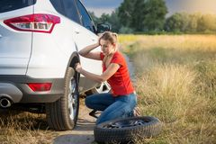 Upset young woman looking on the flat tyre of her car on countryside road. Upset woman looking on the flat tyre of her car on countryside road Stock Photo