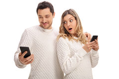 Upset woman looking at her boyfriend's phone Royalty Free Stock Images