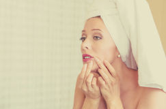 Upset woman looking in a mirror frustrated to see zit on her face, pimple Royalty Free Stock Images