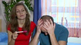 Upset woman is looking in pregnancy test. Frustrated man is sitting next to her stock video footage