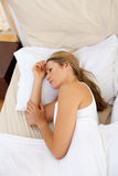 Upset woman lying in bed Stock Photography