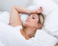 Upset woman lying on bed Stock Photography