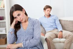 Upset woman with man sitting on sofa in background Stock Photo