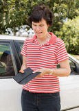 Upset Woman. A middle-aged woman standing near her car looks very upset and cries as she finds her wallet empty of credit cards and money royalty free stock photo
