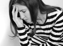 Upset woman monochrome. Young brunette woman with long hair dressed in casual clothes looking depressed Royalty Free Stock Images