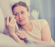 Upset woman with phone Stock Image