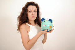 Upset woman with a piggy bank Royalty Free Stock Photo
