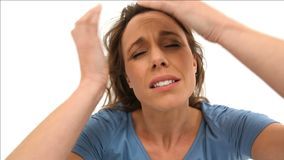 Upset woman placing her hands on her temples. Against a white background stock video