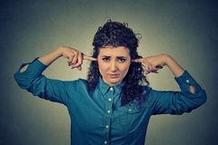 Upset woman plugging ears with fingers doesn't want to listen Stock Photography