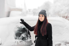 Upset Woman Removing Snow from a Car Window. Funny unlucky pouty girl in front of a frozen auto Stock Photo