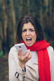 Upset woman shouting to smartphone stock image