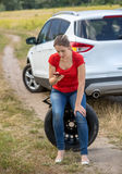 Upset woman siting on spare tire next to broken car at field and Stock Photos