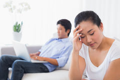 Upset woman sitting on couch while boyfriend uses laptop Stock Photos