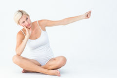 Upset woman sitting on the floor raising her arm Royalty Free Stock Image