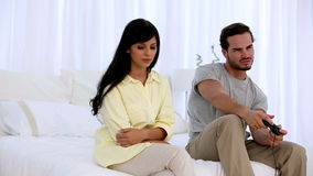 Upset woman sitting next to her boyfriend playing at video game. In the bedroom stock video footage