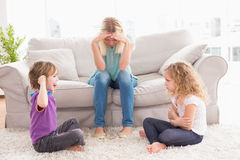 Upset woman sitting on sofa while brother teasing sister. Upset women sitting on sofa while brother teasing sister at home royalty free stock photos