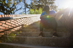 Upset woman sitting on staircase in the boot camp. On a sunny day Royalty Free Stock Photo