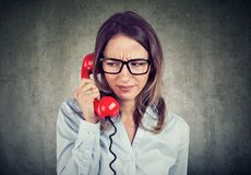 Upset woman speaking on telephone royalty free stock image