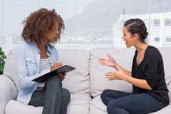 Upset woman speaking to her therapist. Upset women speaking to her therapist while she is taking notes Royalty Free Stock Photos