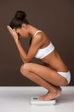 Upset woman standing on weigh scale. Stock Image