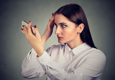 Upset woman surprised she is losing hair has receding hairline. Human emotion stock photography