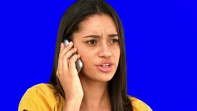 Upset woman talking on the phone on blue screen. In slow motion stock video footage