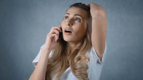 Upset woman talking on the phone isolated on grey background. Worried woman with a serious expression talking about bad news on her mobile phone stock footage