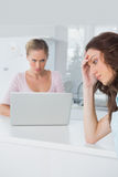 Upset woman thinking while her angry friend is looking at her Royalty Free Stock Image
