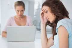 Upset woman thinking while her angry friend is staring at her Stock Photos