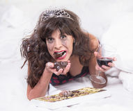 Upset Woman in Tiara Drinking Wine and Gulipng Down Chocolates i Royalty Free Stock Images