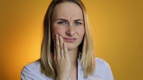 Upset woman with a toothache against on yellow background.  stock footage
