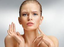 Photo of attractive woman with anti aging cream. Upset woman touching her face. Photo of attractive woman with anti aging cream on grey background. Beauty & Skin Royalty Free Stock Images
