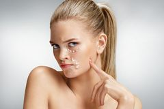 Photo of attractive woman with anti aging cream. Upset woman touching her face. Photo of attractive woman with anti aging cream on grey background. Beauty & Skin stock image