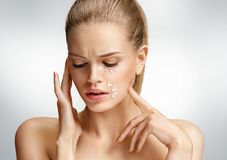 Upset woman touching her face. Photo of attractive woman with anti aging cream. On grey background. Beauty & Skin care concept Royalty Free Stock Photo