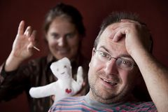 Upset woman with vioodoo doll and guilty man Royalty Free Stock Images