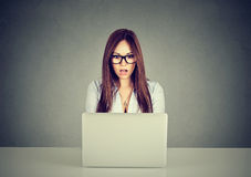 Upset woman watching media content in a laptop online sitting at table Royalty Free Stock Photography