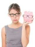 Upset woman wearing glasses holding piggy bank. Expensive eyewear glasses concept. Young female business woman isolated on white background Stock Photography