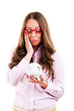 Upset woman wearing glasses holding piggy bank Royalty Free Stock Photos