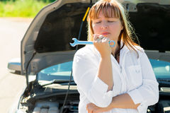 Upset woman with wrench near the open hood Royalty Free Stock Photo