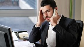 Upset, worried business on phone in office. Serious attractive young businessman sitting at desk in office busy talking on phone and receiving upsetting news stock footage