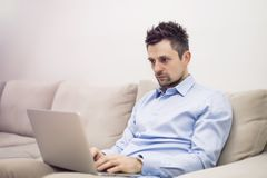 Upset and worried young businessman sitting and working at laptop royalty free stock photography