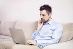Upset and worried young businessman sitting and working at laptop royalty free stock images