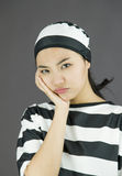 Upset young Asian woman in prisoners uniform with her hands on cheek Royalty Free Stock Photography