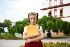 Upset young beautiful female student looking in camera holding folders outdoors, park background. Royalty Free Stock Photos