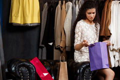 Upset young beautiful girl sitting in shopping mall with buyings. Upset young beautiful african girl sitting in shopping mall, viewing buyings royalty free stock photography