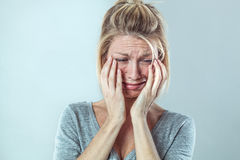 Upset young blond woman crying with big tears expressing sorrow Stock Photos